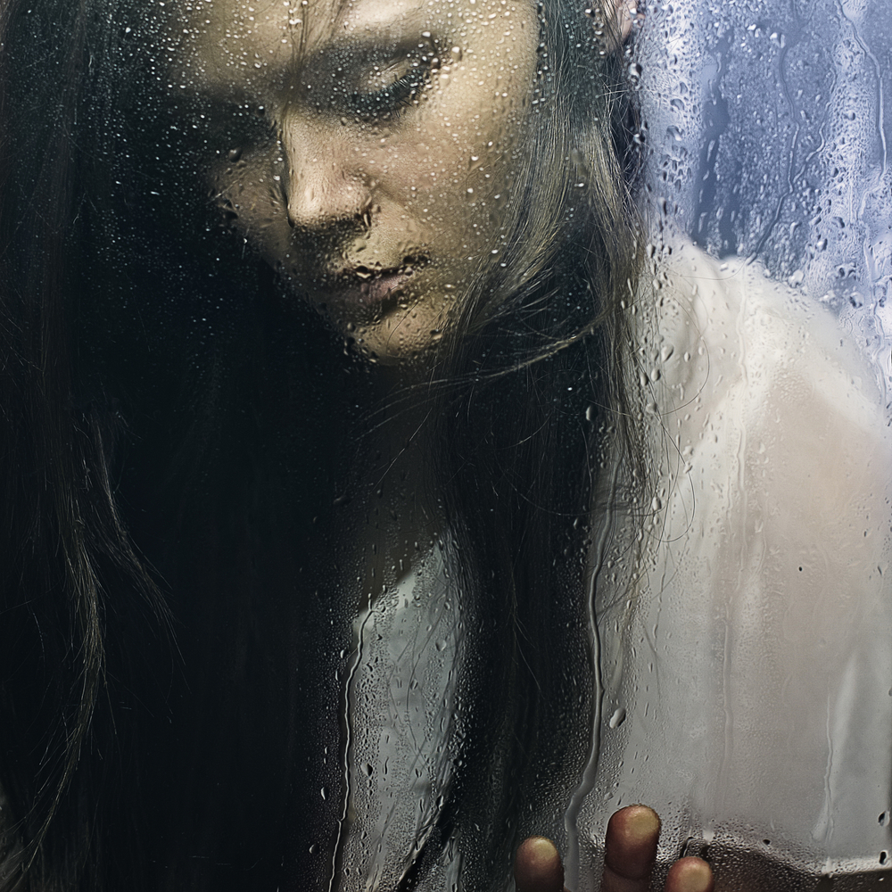 Art portrait of a beautiful young sadly girl standing at the window watching the rain