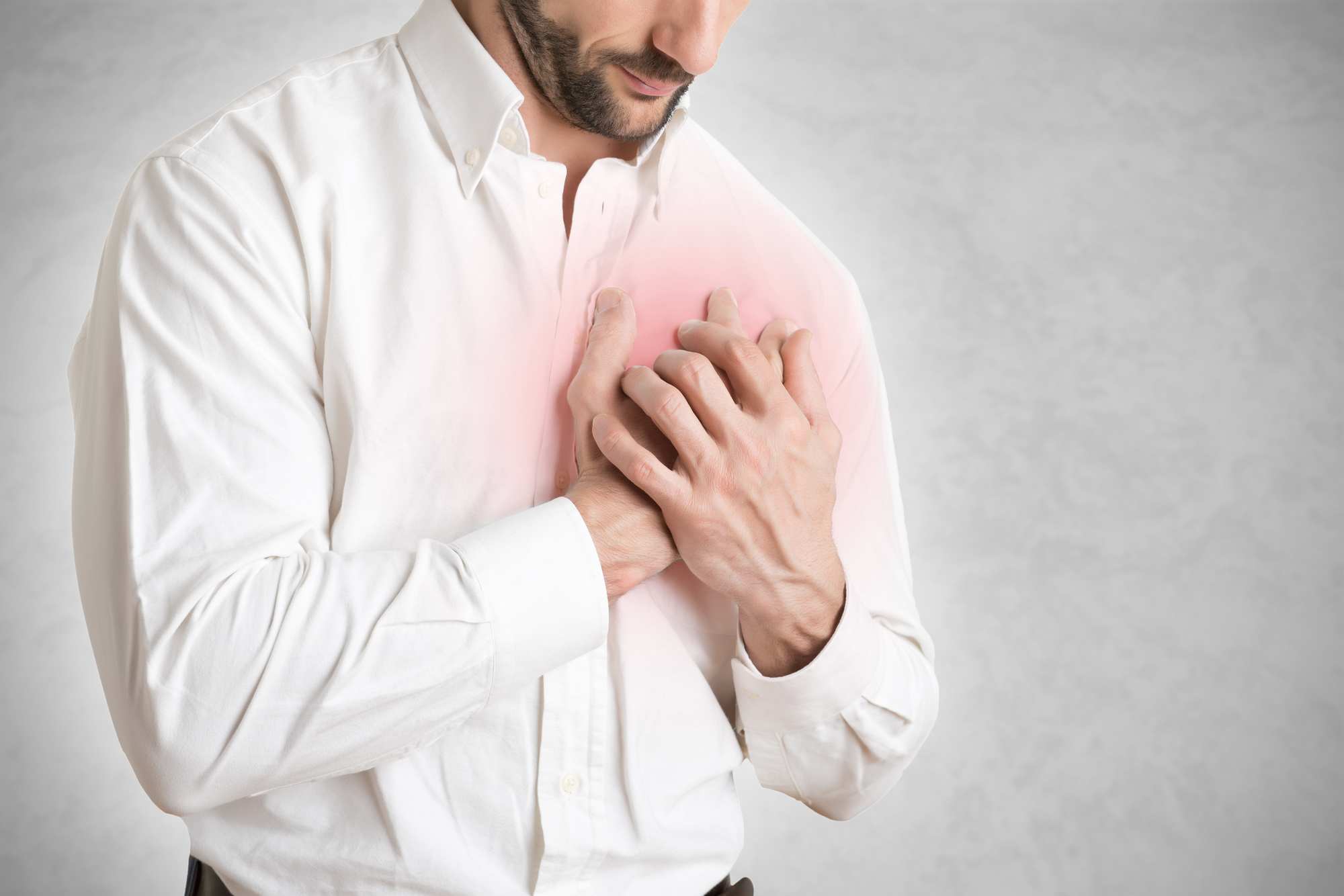 Man having a pain in the heart area, isolated in white, red circle around painful area